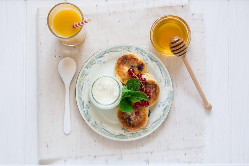 Здоровый завтрак: чизкейки, muesli, югурт, мед, свежие ягоды и сок стоковое изображение