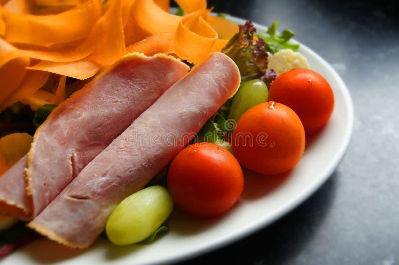 Здоровый салат ветчины, томатов, морковей, бананов, ракеты, оливок салата зеленых и виноградин стоковое фото rf
