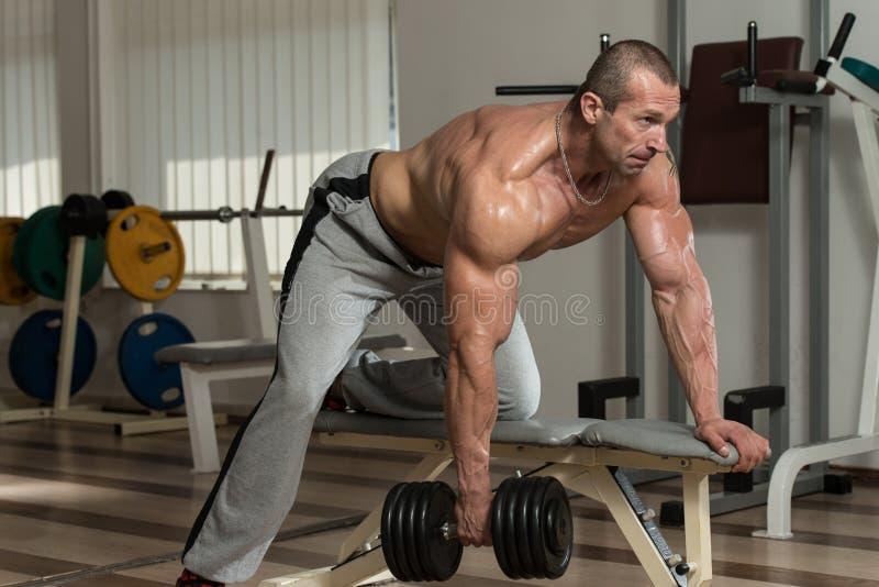 Здоровый человек делая задние тренировки с гантелью стоковые изображения
