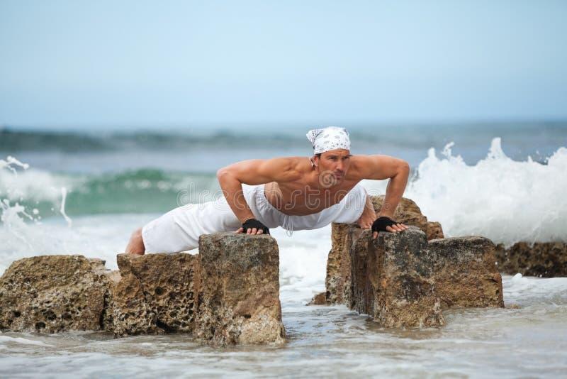 Здоровый человек делая раздумье йоги pilates на лете пляжа стоковая фотография rf
