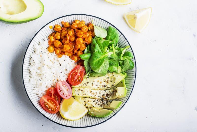 Здоровый шар обеда: basmati рис, нуты в томатном соусе, авокадое, томатах вишни, салате мозоли Взгляд сверху стоковая фотография
