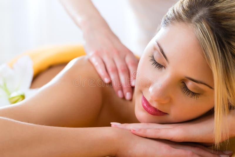 Здоровье - женщина получая массаж тела в курорте стоковое изображение