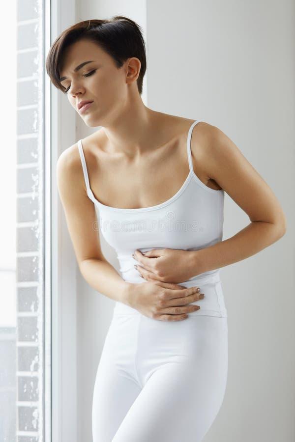 Здоровье женщины Красивая женская боль чувства в животе стоковые изображения