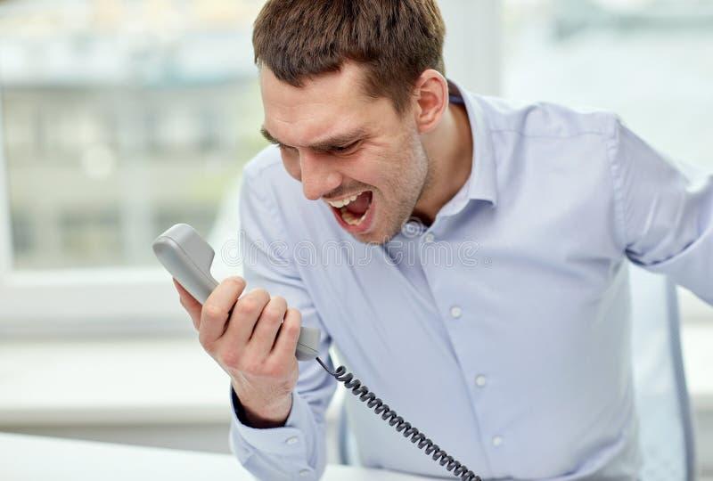 Злющий бизнесмен вызывая на телефоне в офисе стоковые фото