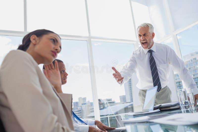 Злющий босс выкрикивая на коллегах стоковые изображения