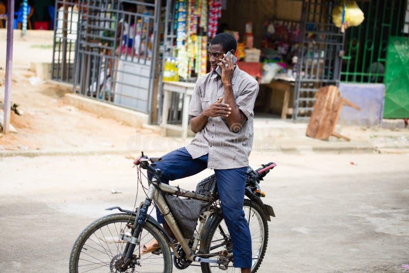 Ивуарский человек связывает с его мобильным телефоном стоковая фотография