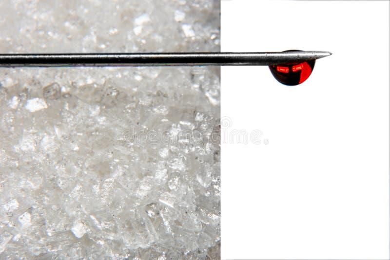 Игла с падением крови на кубе сахара изолирована на белой предпосылке стоковые изображения