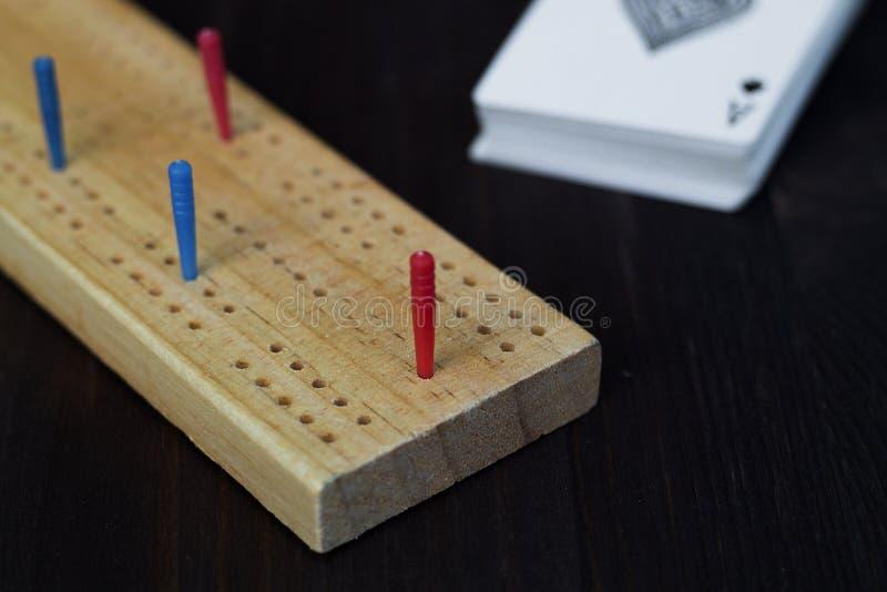 Игральные карты и доска cribbage на черной предпосылке стоковые фотографии rf