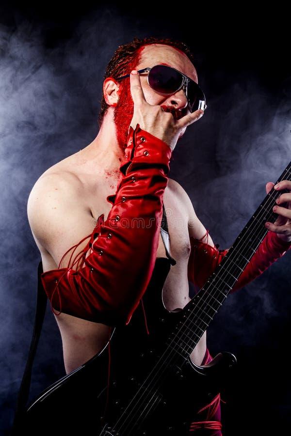 Играть, гитарист с чернотой электрической гитары, нося болью стороны стоковая фотография