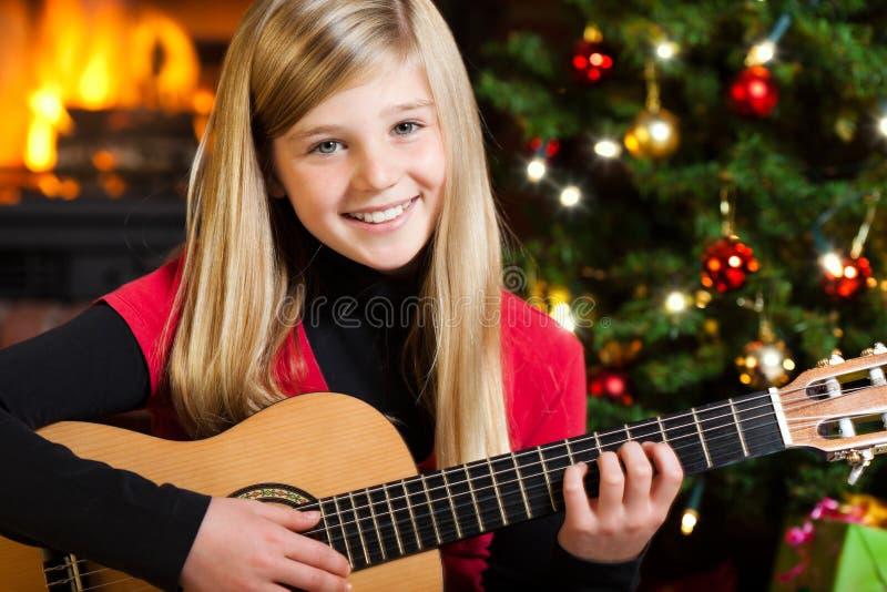 играть гитары девушки Рожденственской ночи стоковое изображение
