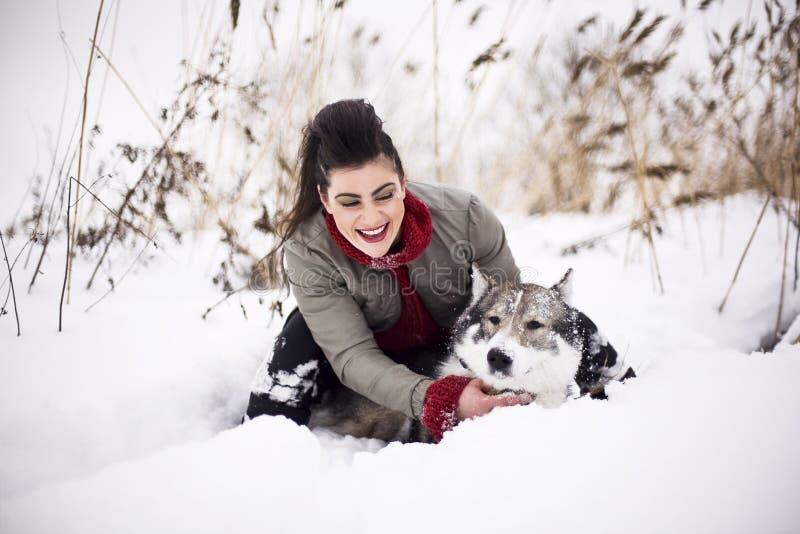 Играть молодой девушки моды идя с осиплой собакой снаружи в парке снега зимы, имеющ потеху совместно, люди образа жизни стоковые фотографии rf