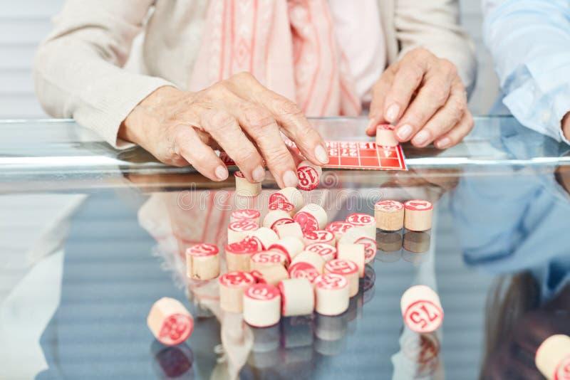 Играть руки старшиев играя bingo стоковое изображение