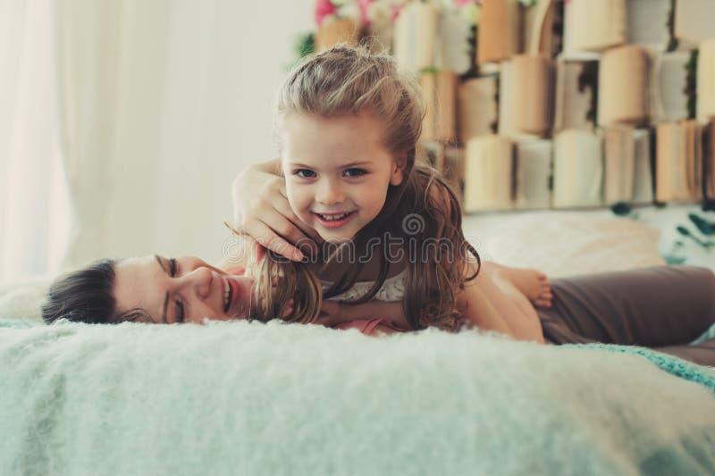 играть семьи счастливый домашний Дочь матери и малыша ослабляя и имея потеху в кровати стоковая фотография rf