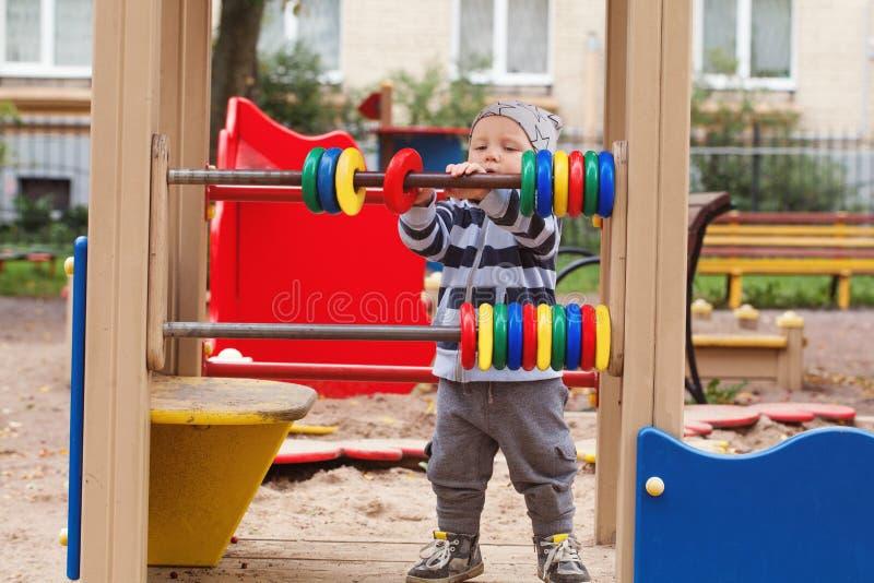 играть спортивной площадки ребенка Ребенк в спортивной площадке outdoors стоковая фотография rf