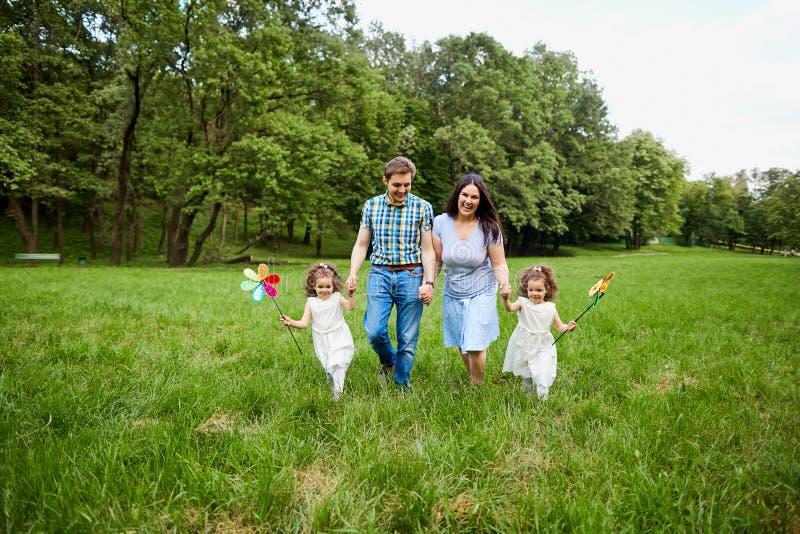 Играть счастливой семьи идя в парке лета стоковые фотографии rf