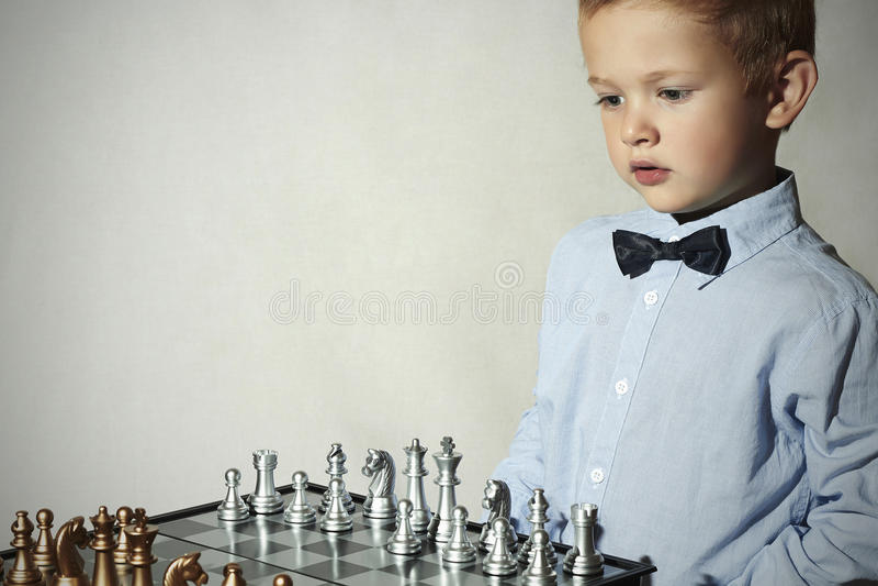 играть шахмат мальчика малыш франтовской Маленький ребенок гения Умная игра chessboard стоковое фото