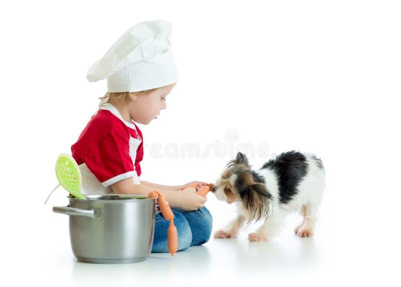 играющая Рол игра Мальчик ребенк играет шеф-повара с собакой Кашевар weared ребенком подает голодный щенок стоковое изображение