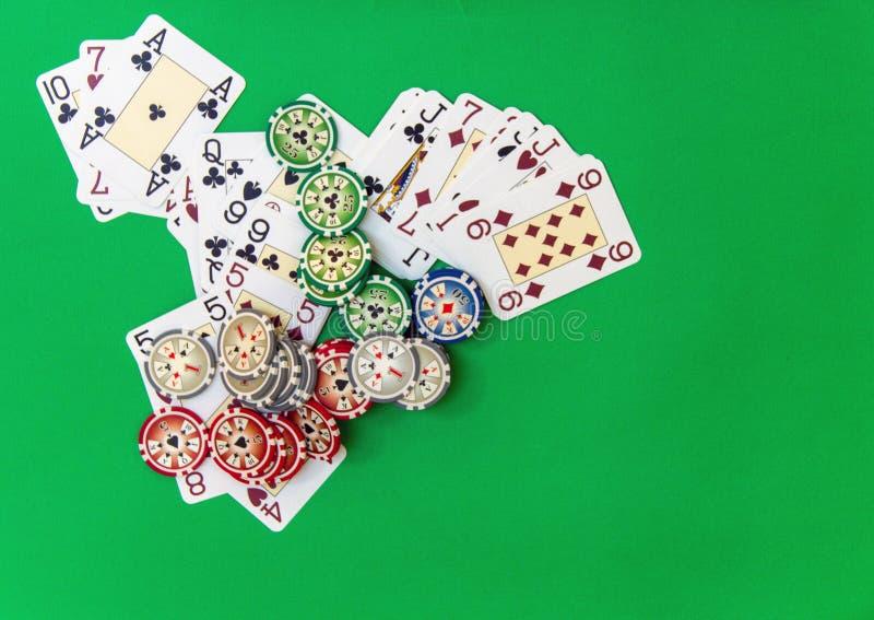 Играя в азартные игры стог и игральные карты обломоков на зеленой таблице стоковые изображения