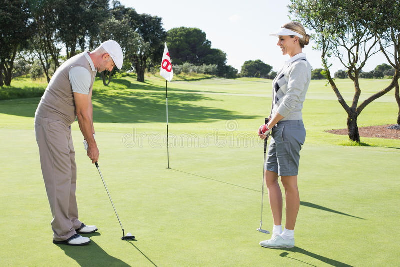 Играя в гольф пары на зеленом цвете установки на восемнадцатом отверстии стоковые изображения