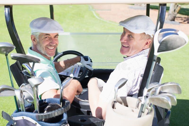 Играя в гольф друзья управляя в их багги гольфа усмехаясь на камере стоковое изображение