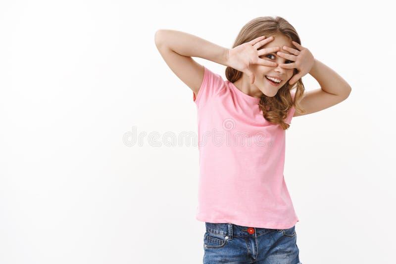 Играя на пальцах, накрывая глаза ладонями, улыбаясь и радостно смеясь, улыбаясь, играя стоковые изображения rf