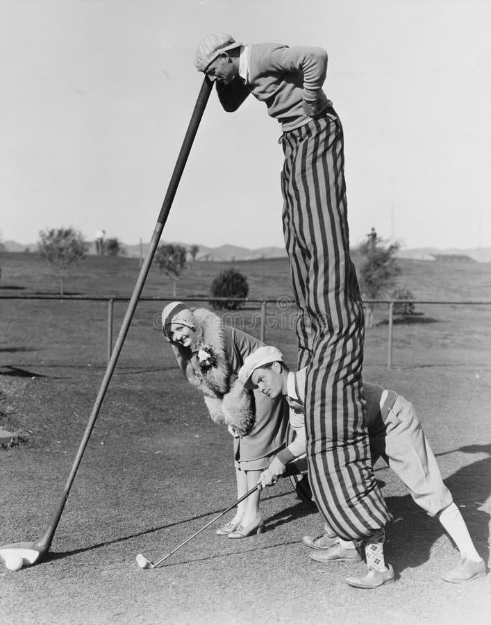 Игра гольфа с человеком на ходулях (все показанные люди более длинные живущие и никакое имущество не существует Гарантии поставщи стоковое фото