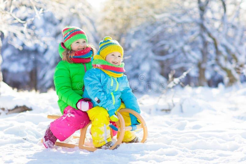 Игра детей в снеге Езда скелетона зимы для детей стоковые фото
