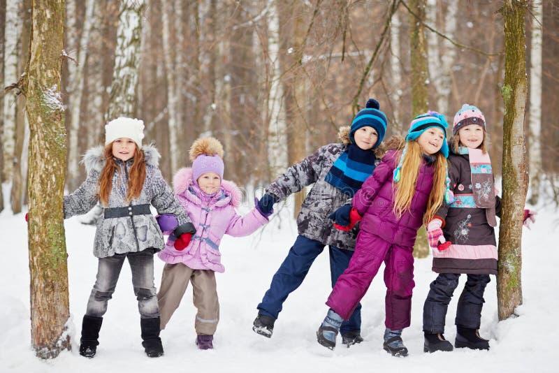 Игра детей в парке зимы стоковые фото