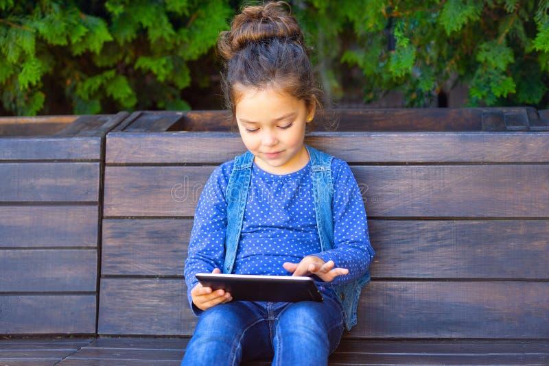 Игра маленькой девочки в планшете outdoors Работать снаружи с техником стоковые фото