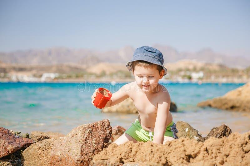 Игра мальчика с песком на пляже лета стоковые изображения rf
