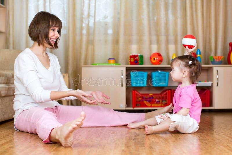 Игра матери и ребенк с шариком внутри помещения стоковые изображения rf