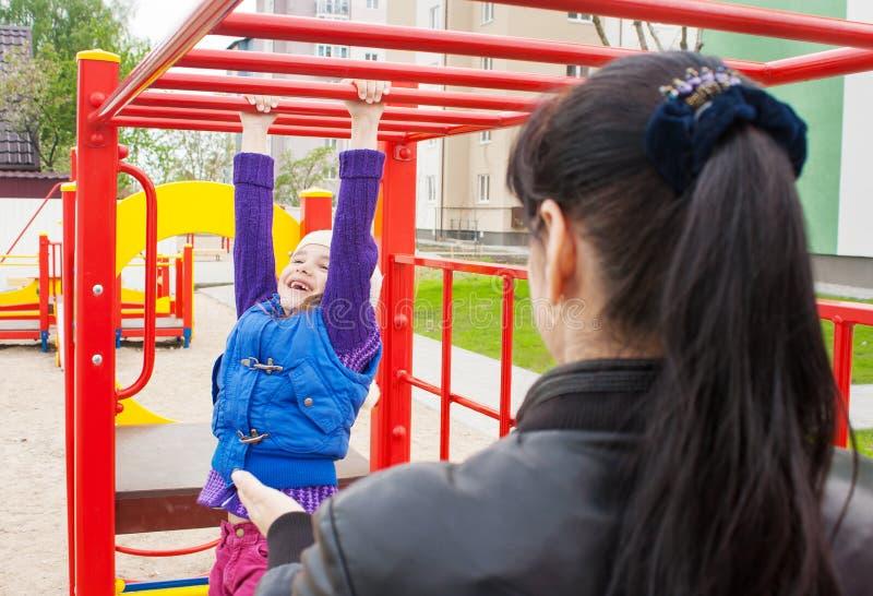 Игра матери наблюдая на дочери спортивной площадки стоковые изображения