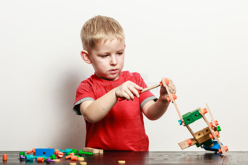 Игра мальчика с игрушкой на таблице стоковое фото
