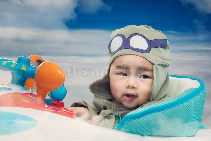 Игра младенца на игрушке самолета на небе стоковое фото