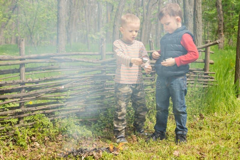 Игра 2 молодая мальчиков наряду с куря огнем стоковое изображение