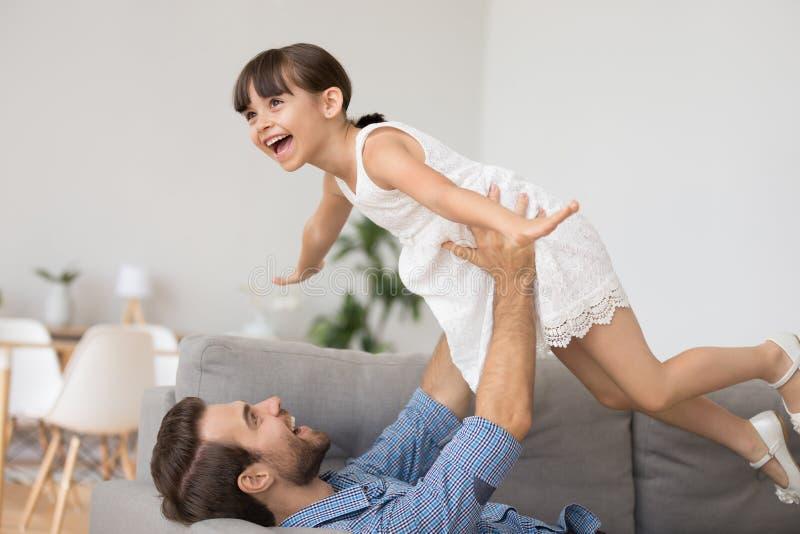 Игра отца с меньшим владением дочери она поднимаясь вверх стоковая фотография