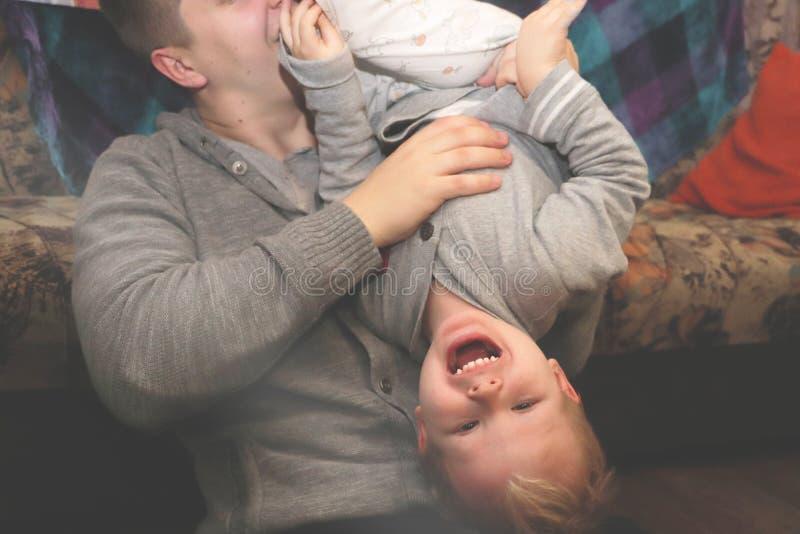 Игра папы и сына, потакает Отец повернул его сына вверх ногами, смех ребенка стоковая фотография rf