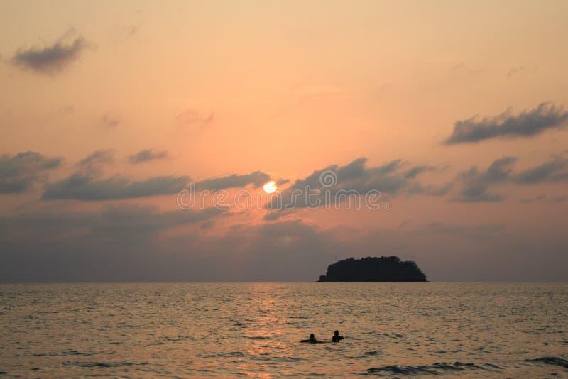 Игра пар на заходе солнца и острове стоковое изображение rf