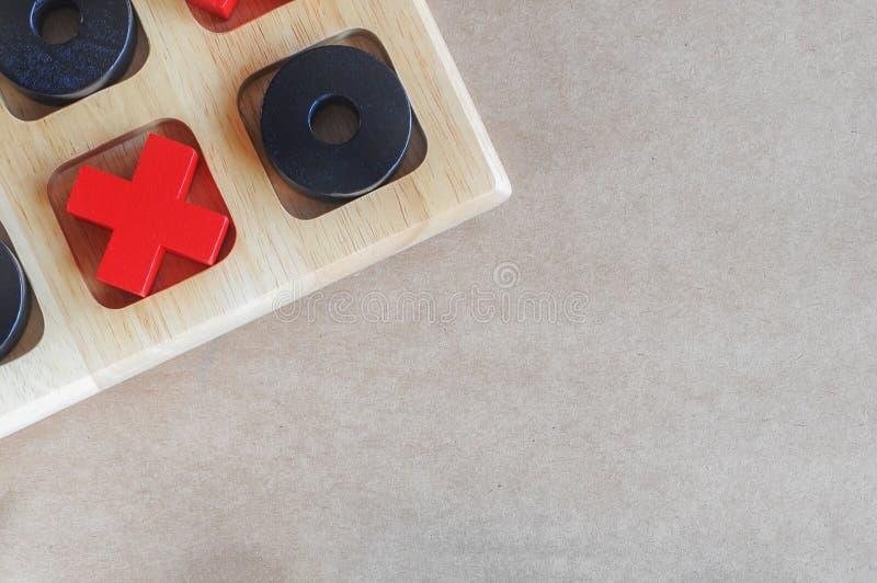 Игра пальца ноги tac конца-вверх деревянная tic на бумажной коричневой предпосылке, плоской концепции положения стоковое фото