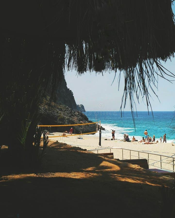 Игра пляжа лета Взгляд от тени Люди на волейболе игры пляжа Красивое голубое море с горами и утесами стоковые изображения rf