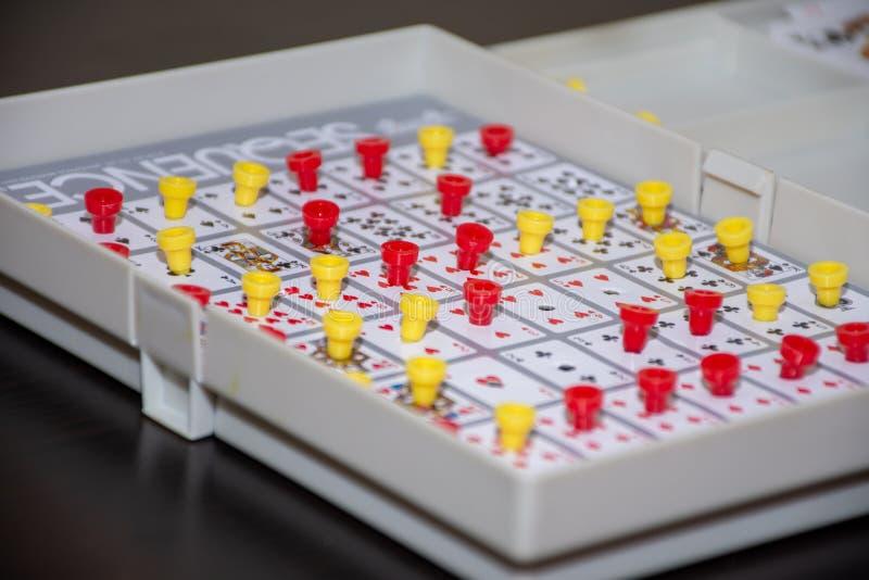 Игра последовательности карты потехи семьи показывая настольную игру с желтыми и красными колышками создавая последовательность и стоковое фото rf
