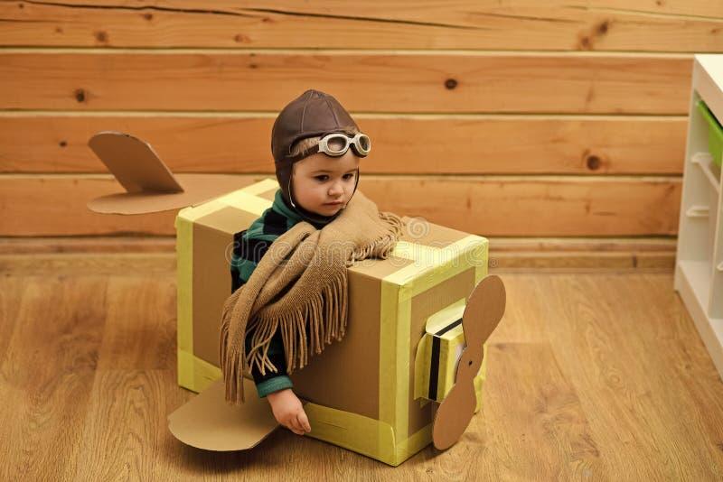 Игра ребенк Счастливый мальчик сидя в плоскости картона стоковые изображения rf