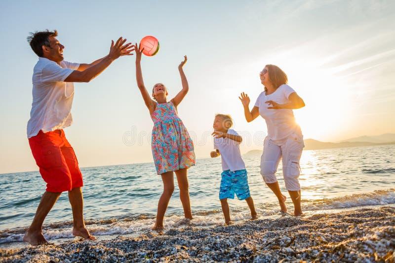 Игра семьи на пляже стоковое фото rf