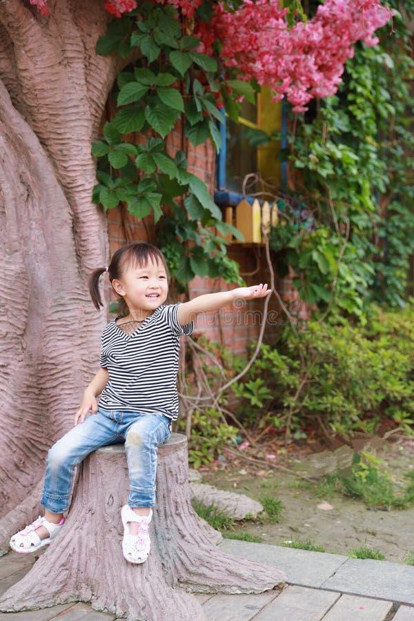 Игра смеха улыбки ребенка маленькой милой симпатичной девушки китайская и имеет потеху на детстве счастья природы парка лета стоковое фото rf