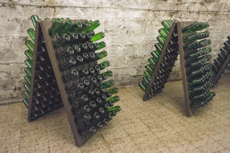 Игристое вино постарето в бутылках на стойках стоковые изображения