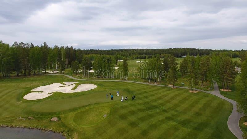 Игроки в гольф ударяя съемку гольфа с клубом на курсе пока на летних каникулах, воздушных стоковое фото