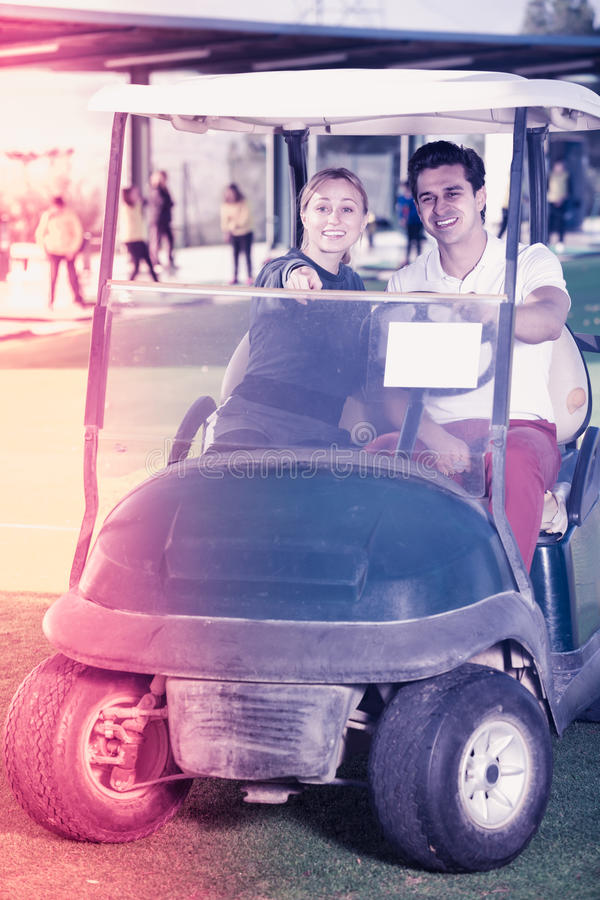 Игроки в гольф молодого человека и женщины ехать тележка гольфа стоковое изображение