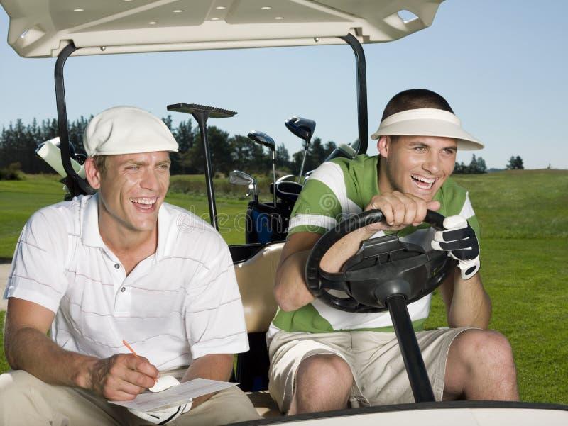 Игроки в гольф сидя в тележке гольфа стоковое фото rf