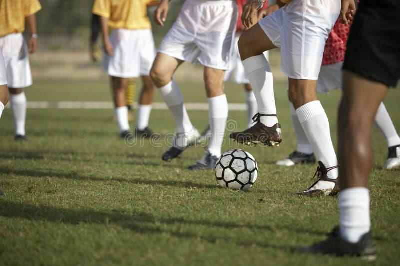 Игроки играя футбол стоковые фотографии rf
