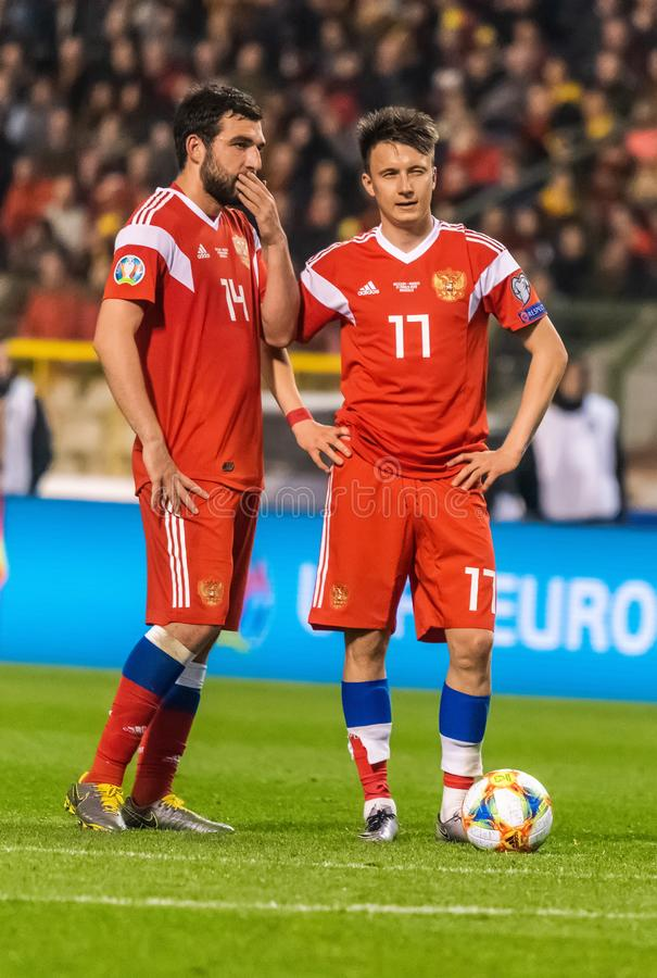 Игроки национальной команды Georgi Dzhikiya и Aleksandr России Golovin выполняя свободный удар во время квалификации 2020 евро UE стоковые изображения
